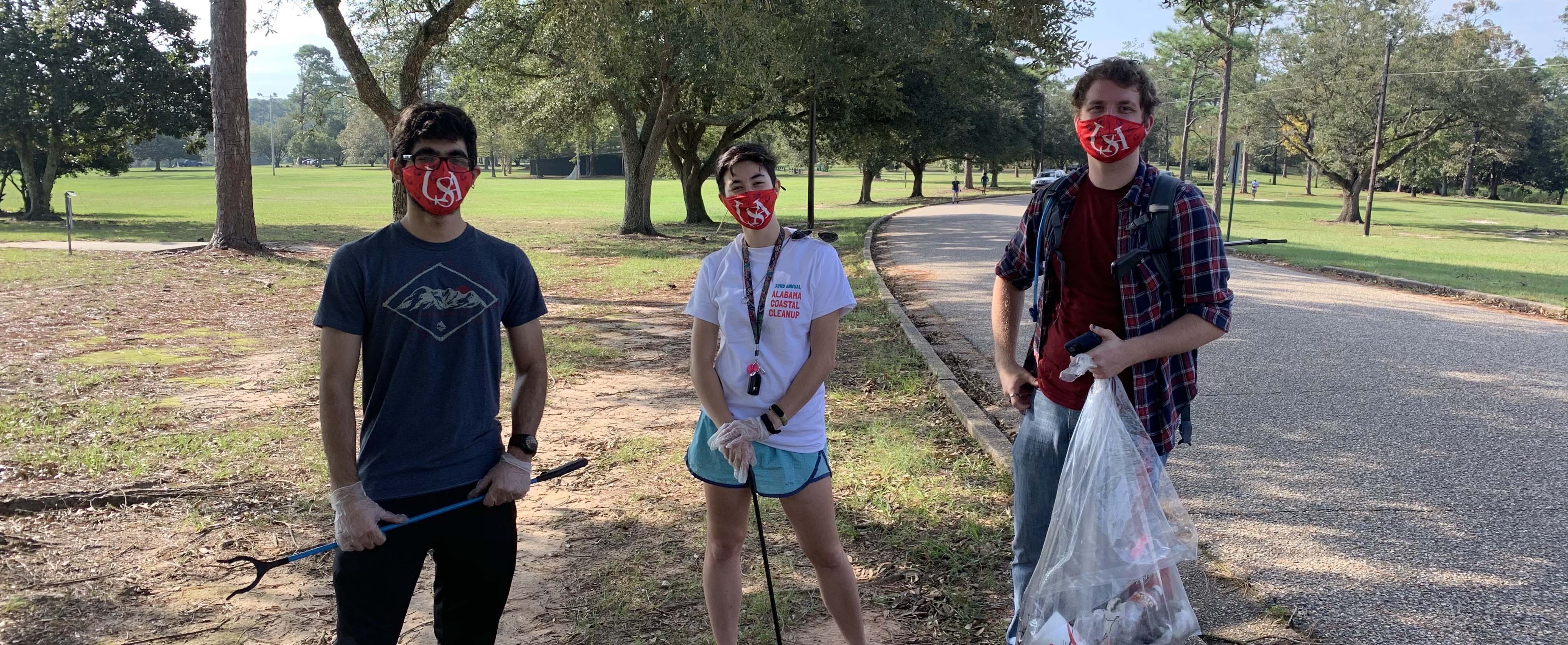 Three AED 2020-21 members working together to clean up Langan Park at Coastal Cleanup