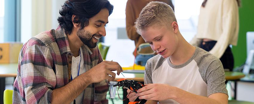 A man helping a younger student on a project