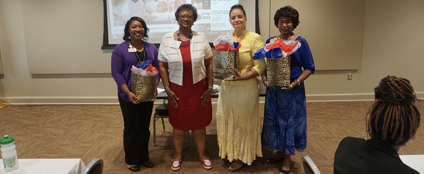 Four females holding gift bags.
