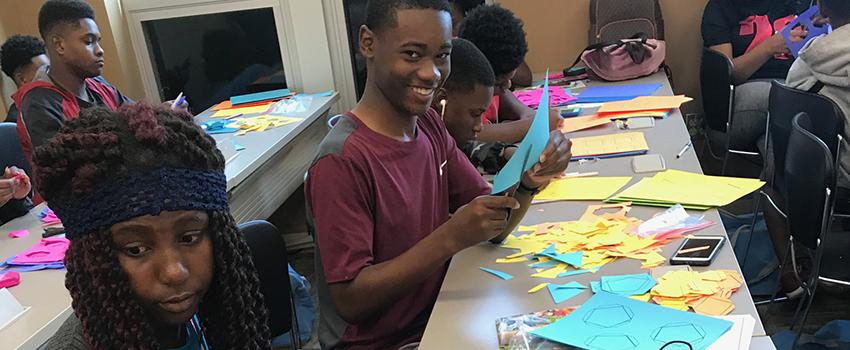Male student smiling working on paper project