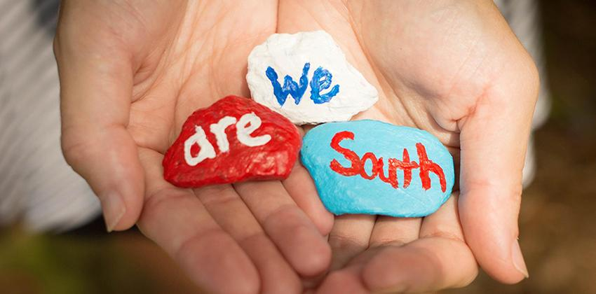 Hands holding We Are South painted rocks