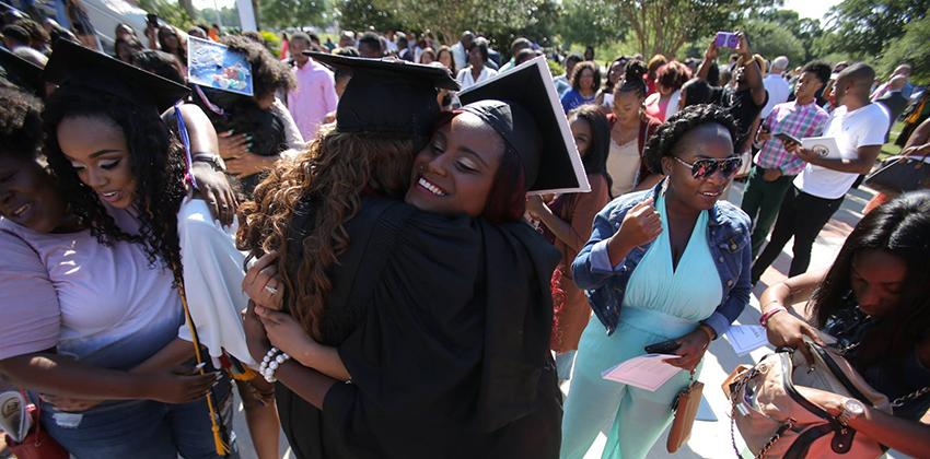 Two students hugging during graduation