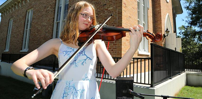 Student playing Violin in front of Honors