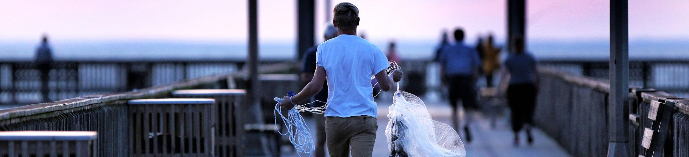 Male carrying cast nets on Fair Hope Pier
