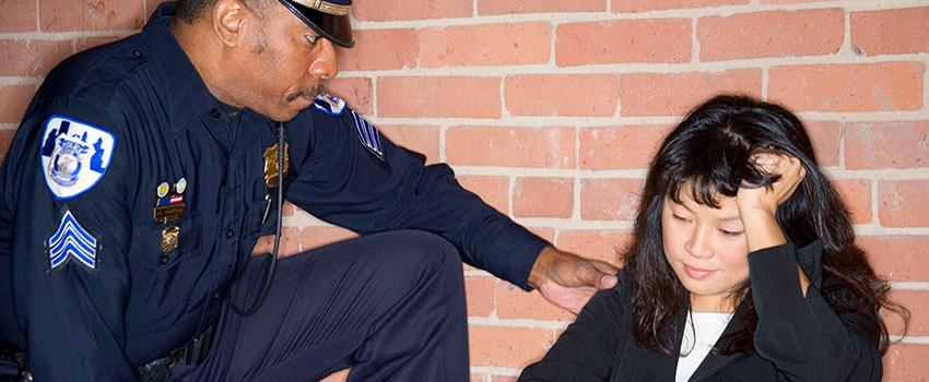 Police Officer helping a woman sitting on the floor