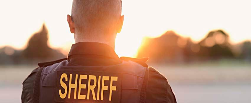 The back of a sheriff looking out at the sun