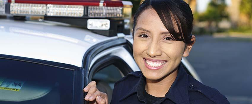 Smiling Female Police Officer in front of her car