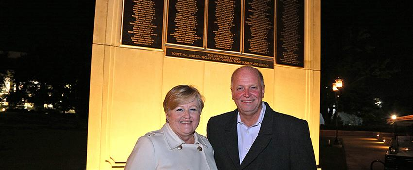 A male and female alumni in front of wall of honor
