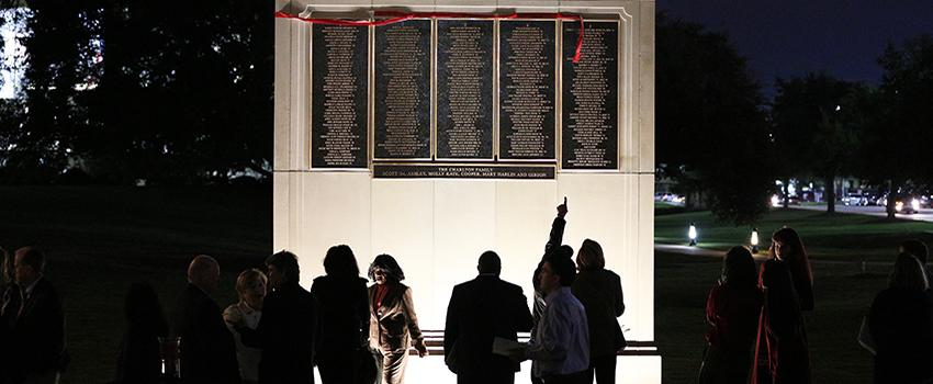 Alumni pointing at Wall of Honor
