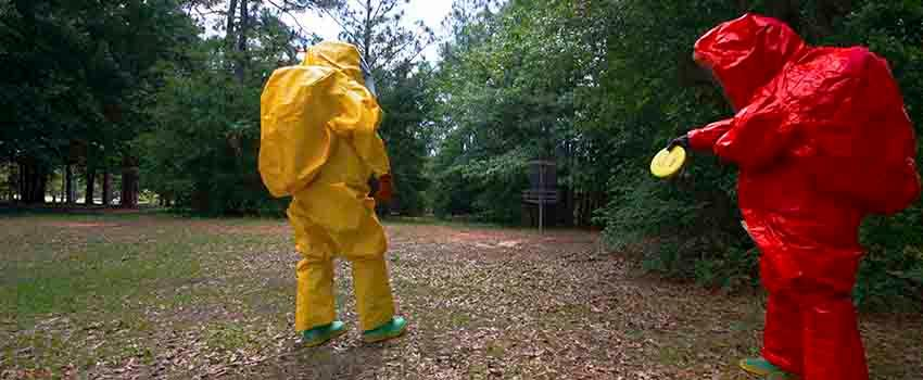 Two men in hazmat suits in disc golf courseTwo men in hazmat suits in front of storage container
