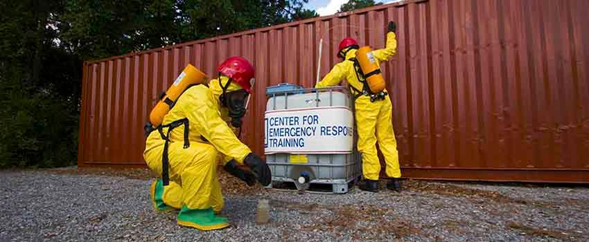 Two men in hazmat suits in front of storage container