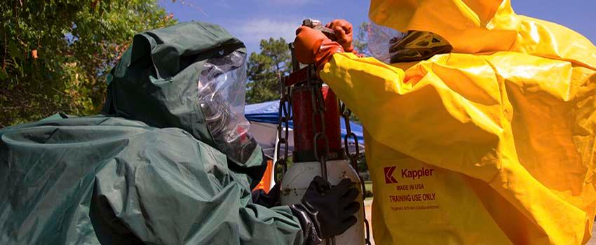 Two men in hazmat suits in working with equiment