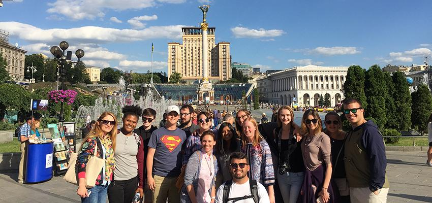 """Kiev. This picture is on Independence Square where both the 2004 Orange Revolution and 2014 Euro Maidan Revolution (Revolution of Dignity). The students are pictured with our local contact, Inna, and our guide, Galina. Inna was part of the protests and had family on both sides during the Euro Maidan Revolution. Galina was a journalist who was right in the middle of all of the protests and witnessed history firsthand. A few nights later, we actually had dinner in a speakeasy below our feet. It's hidden under the square and it's called The Last Barricade. The theme of the restaurant is revolution so the password to get in was the Ukrainian phrase """"always fight""""."""
