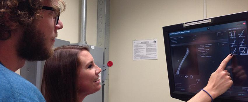 Male and female student looking at monitor