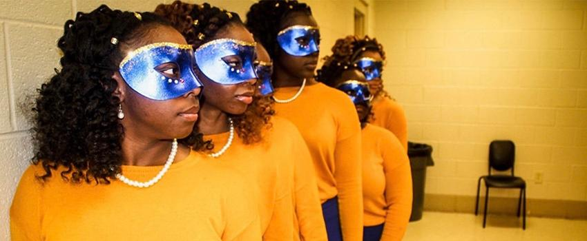 NPHC Female students with purple masks and yellow sweaters on
