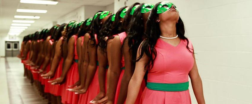 NPHC Studenst in pink dresses with green sashes looking up
