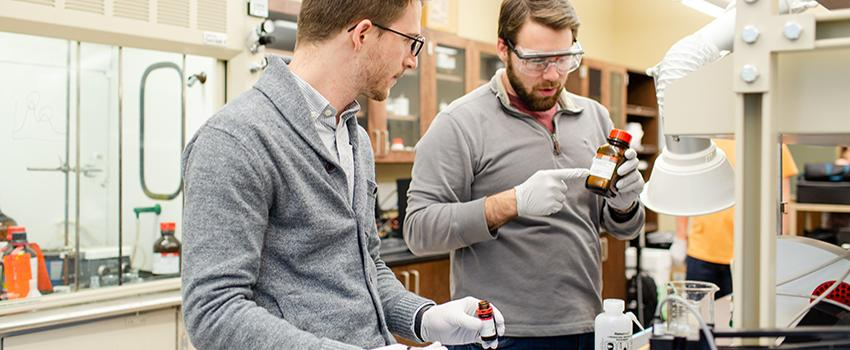 Two males looking at bottle in chemical engineering lab.