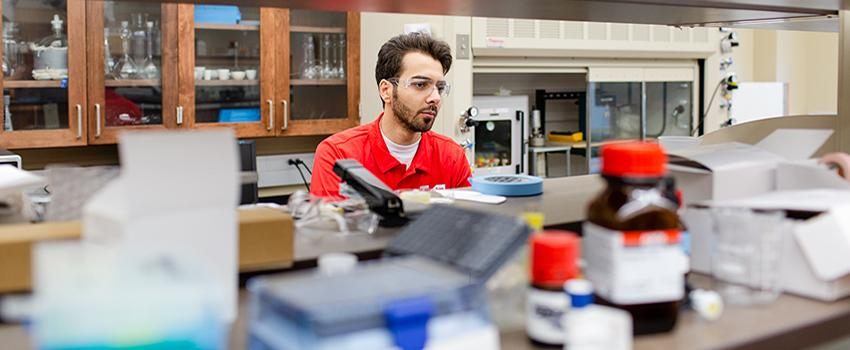 Male student with safety glasses on in a lab.