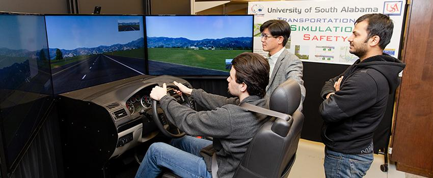 Engineering students using the driving simulator with professor.