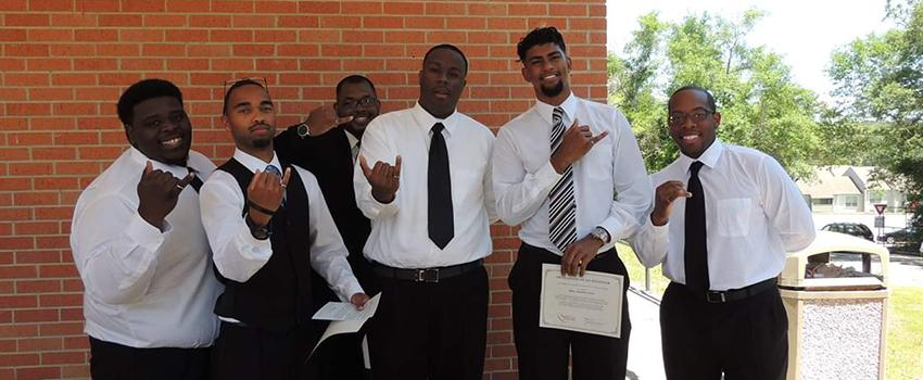 A group of male students holding up their pinky rings.