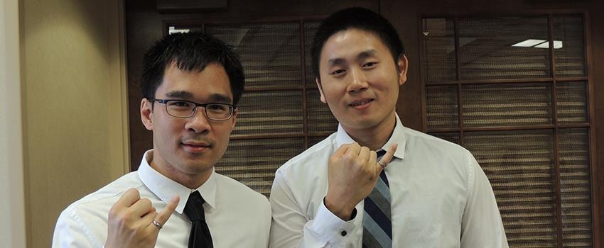 Two male students holding up their pinky rings.