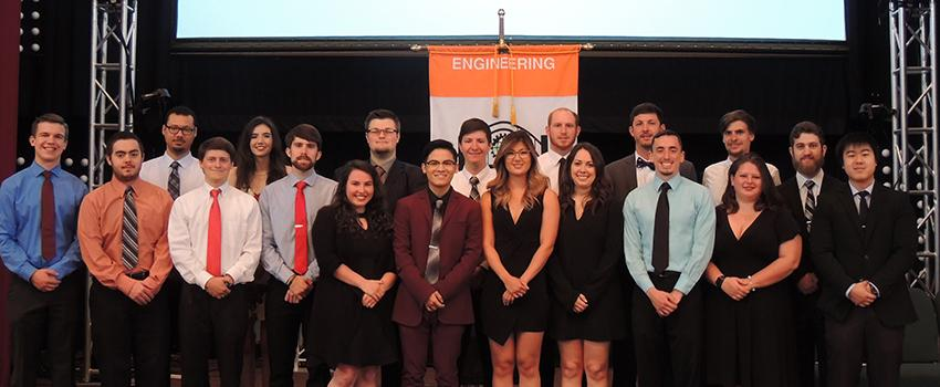Engineering students standing on stage in front of flag.