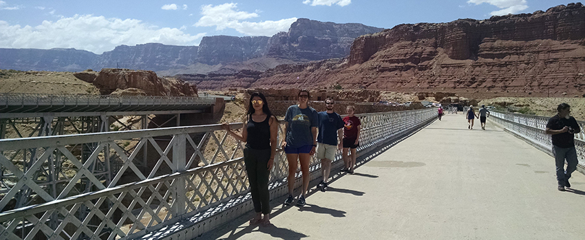 Geology students on a bridge with a mountain view.