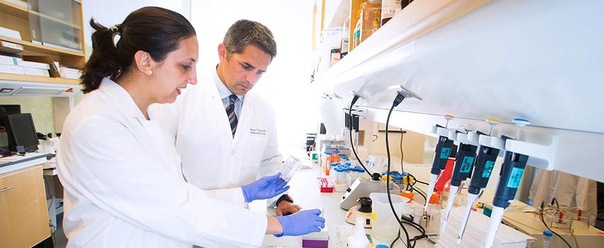 Dr. Rodney P. Rocconi, a gynecologic oncologist and interim director of the USA Health Mitchell Cancer Institute, works in the lab with Dr. Luciana Da Silva Barnes, assistant professor of basic and translational gynecological oncology.