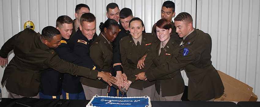 Cadet leaders cutting a cake