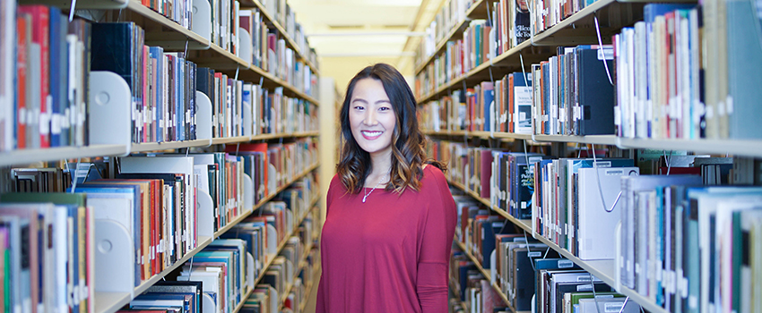 Student standing in rows of books at the library