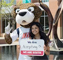 SouthPaw and a USA Student hold a sign that states: We Are Accepting