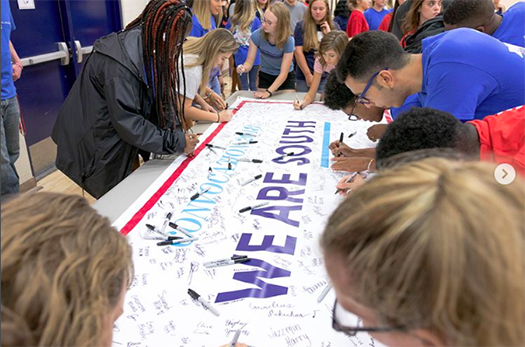 Students signing a banner at Convocation
