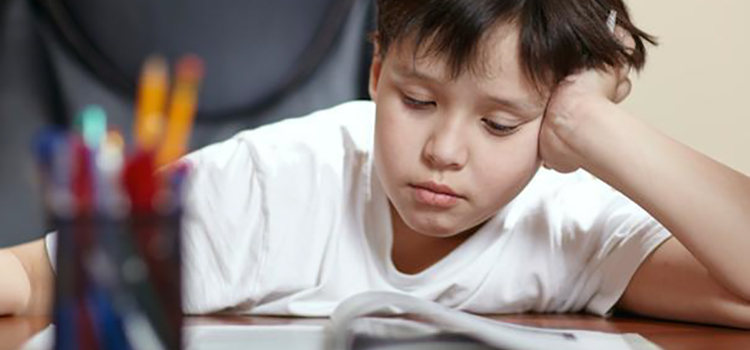 Young child reading at desk