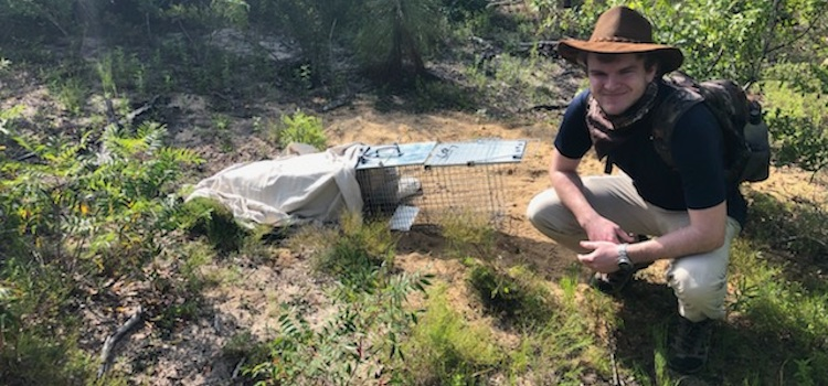 Cade Smelley in the field after setting a live trap over a Gopher Tortoise burrow.