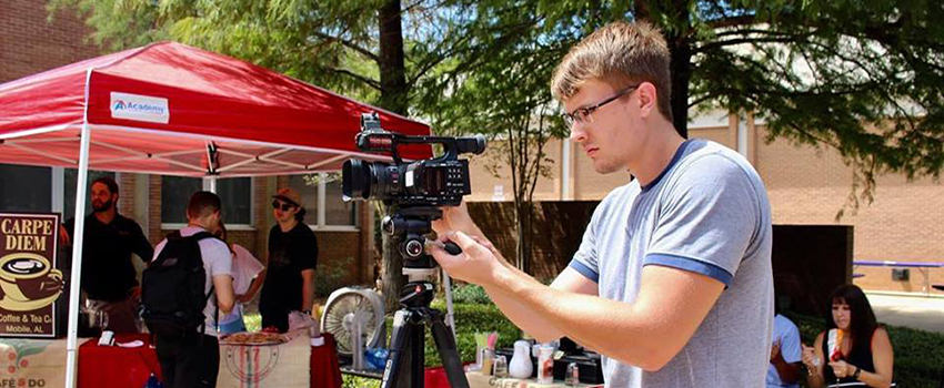Male student working on video camera outside on campus