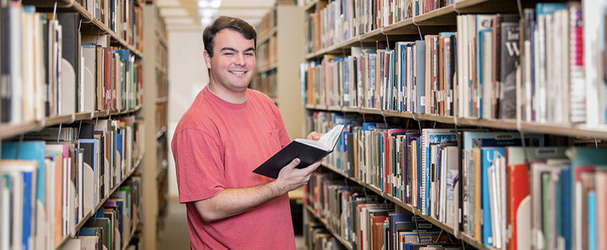 Male student holding a book in the library.