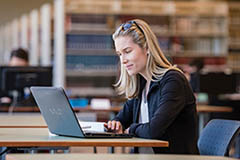 Female working on laptop in library.