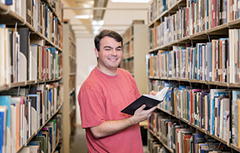 Male student in library holding a book.