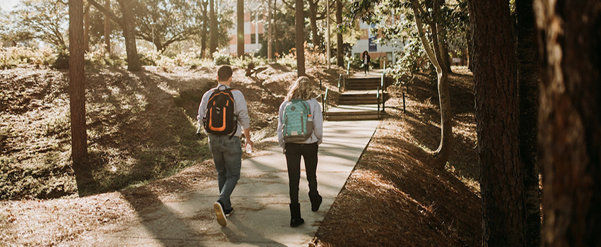 Two students walking toward the arts and sciences building.