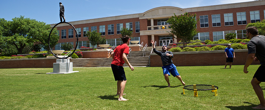 Students playing ball outside of Meisler Hall