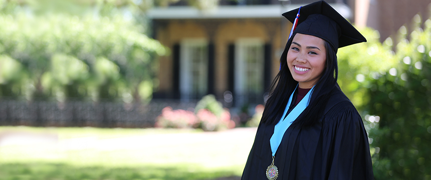 Female student in graduation cap and gown smiling