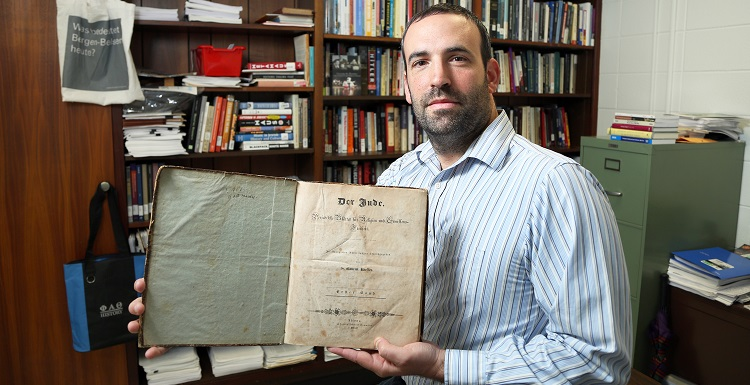 "Dr. David Meola, assistant professor of history, holds the journal ""Der Jude,"" created by Dr. Gabriel Riesser and published in the 1830s to advance Jewish emancipation throughout the German states."