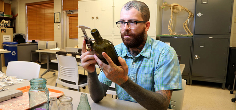 Dusty Norris, a graduate of the University of South Alabama's anthropology program, is using an archaeology tool to record information about one of the artifacts found at the sites of the shotgun houses in areas of downtown Mobile. This preliminary work is being done as plans for the Mobile River Bridge and Bayway project moves forward. data-lightbox='featured'