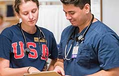 A female in USA shirt and man in scrubs looking at chart with stethoscopes on.