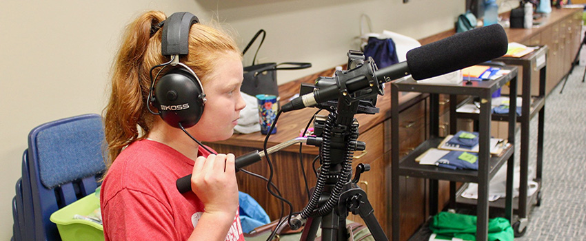 Literacy Summer Camper with headphones on and microphone.