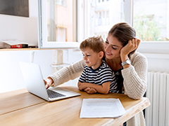 Mother working on lap top with child in lap
