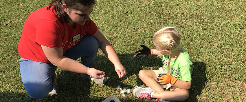 Student teacher working with child in grass on project outside