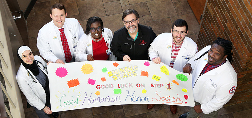 Medical students hold a sign encouraging those taking the Step 1 exam.
