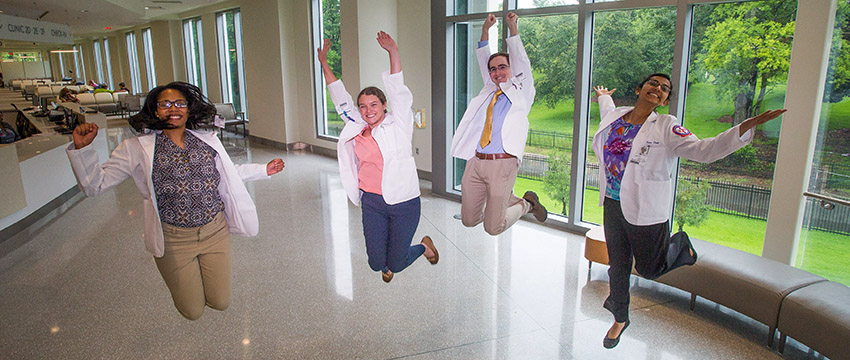 Four third-year medical students jump mid-air at the Strada Patient Care Center during Orientation.