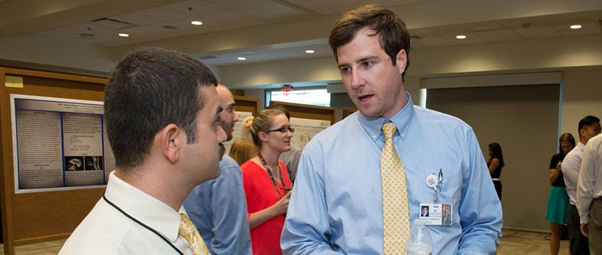 USA medical student Richard Huettemann explains his research to Dr. Philip Almalouf